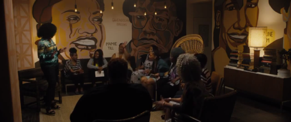 A group of women gather in a secret back room in a bookstore to discuss their protest plans. A mural depicting famous African American women covers the walls of the room.